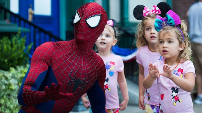 Spider Man strikes a kneeling action pose as 3 little girls look on