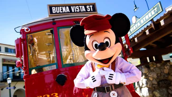 Mickey Mouse standing in front of a Red Car Trolley on Buena Vista Street