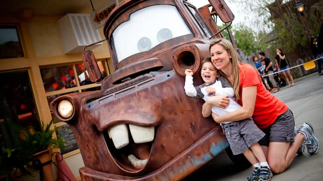 A mother and her young son smiling while they enjoy a Character Greeting with Tow Mater in Cars Land