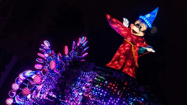 Sorcerer Mickey waves from an illuminated float that shines brightly against the night sky
