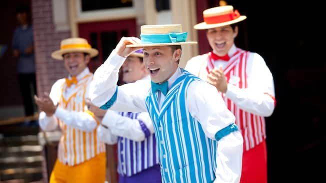 A group of 4 men sing and perform outside wearing boater hats, arm garters and striped vests