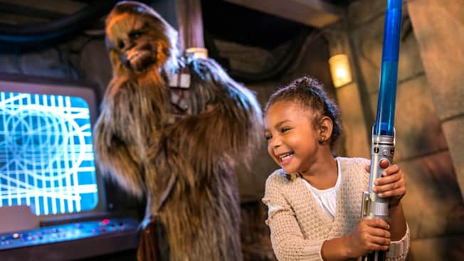 A smiling young girl grips a light saber as Chewbacca looks on