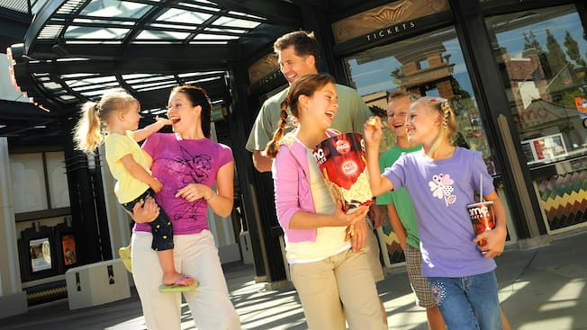 Families share smiles and movie popcorn after exiting AMC 12 Theatres