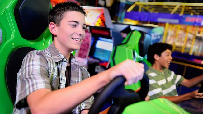 A teen boy plays an ESPN Zone Sports Arena driving game at Disneyland Resort