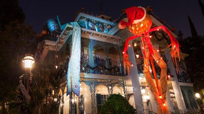 Espantapájaros temible, con cabeza de calabaza y un gorro de Santa, enfrente de Haunted Mansion