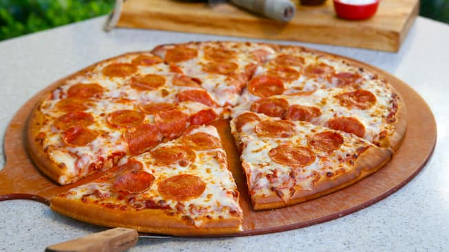 A fresh out of the oven, sliced pepperoni pizza on a wooden pizza board sits on a table outdoors