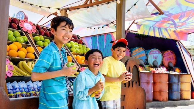 Tres niños felices seleccionan fruta en el puesto de antojitos Fillmore's Taste-In en Disney California Adventure Park