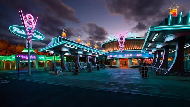 Gas station-themed entrance to Flo's V8 Cafe lit with neon signs at night
