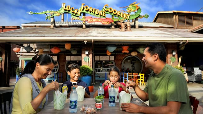 A family of 4 dines outside near the sign: Lucky Fortune Cookery Pacific Rim Foods