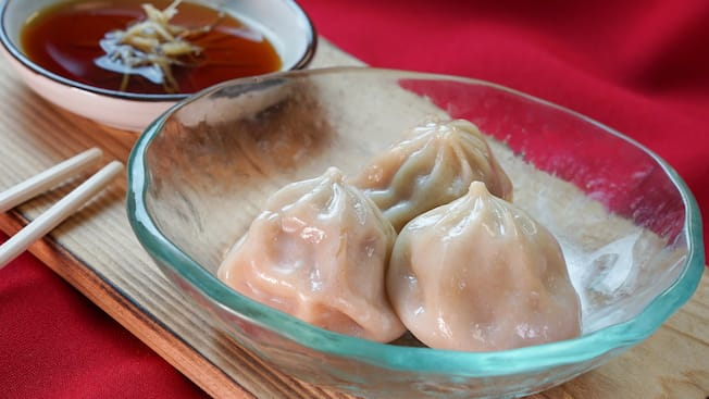 Steamed vegetable dumplings next to a sesame garlic soy dipping sauce