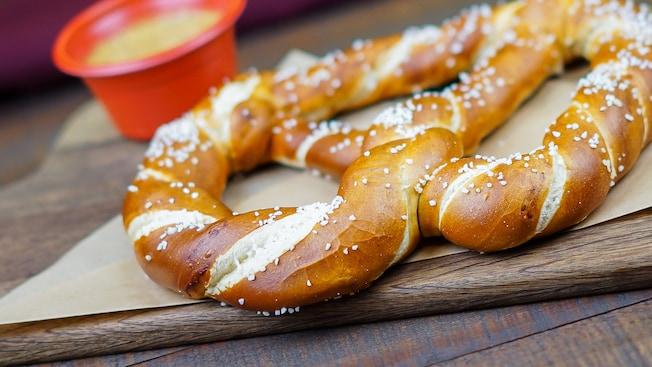 A stack of 6 freshly baked hot Bavarian pretzels are lightly sprinkled with salt
