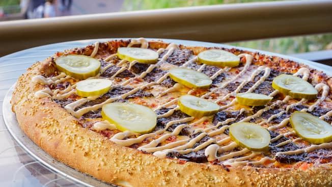 A thick sesame seed crusted cheeseburger pizza is covered with pickle slices, meat and dressing drizzles