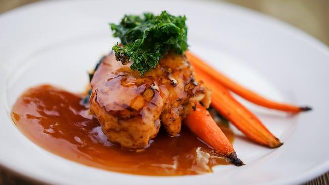 Un plato de pollo de Bourbon Street con vegetales condimentados y salsa de bourbon de Café Orleans