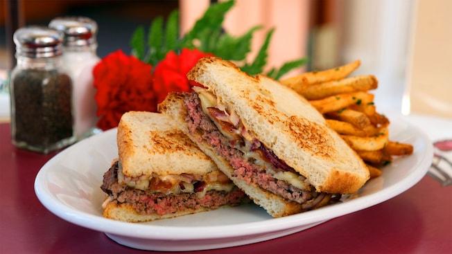 Un plato con un sándwich de tocino y queso derretido en un pan de masa fermentada, más papas fritas de Carnation Cafe