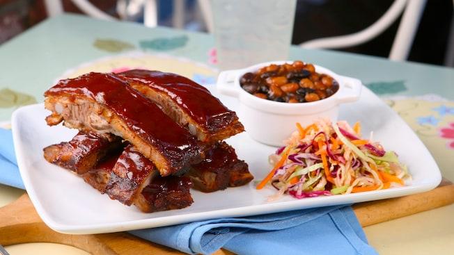 Un plato de costillas de cerdo adobadas con picante, con frijoles horneados y ensalada de col reposa en una mesa al aire libre en River Belle Restaurant