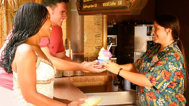 A man is excited to receive his pineapple treat at Tiki Juice Bar at Disneyland Park