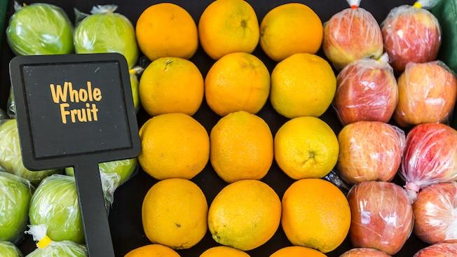 Un carro de frutas con manzanas y naranjas