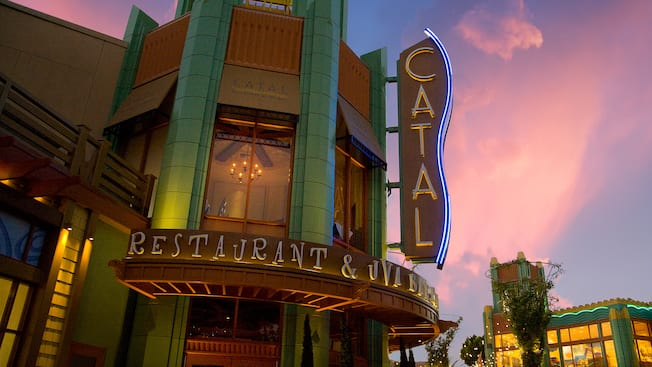 The neon Catal Restaurant & Uva Bar sign lights up as the sun sets over Downtown Disney District