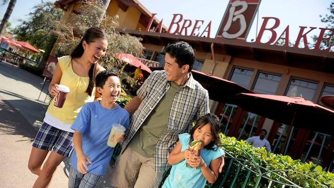 Una familia de cuatro personas se ríe mientras disfruta de una variedad de golosinas de La Brea Bakery Express