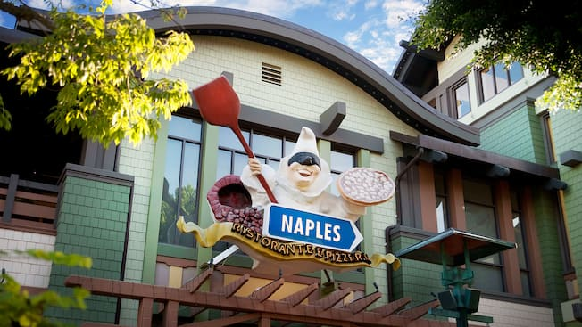 Sign for Naples Ristorante e Pizzeria features a whimsical harlequin holding a pizza