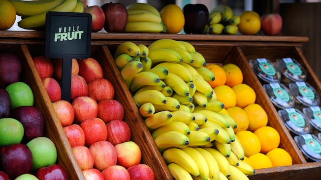 A fruit stand with apples, bananas and oranges