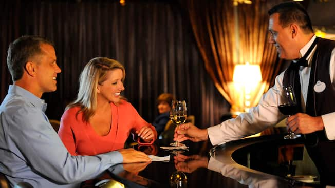 A bartender presents glasses of wine to a happy couple at Steakhouse 55 Lounge