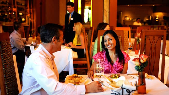 A couple gaze lovingly at each other during an evening meal at Napa Rose