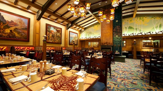 Disneyland dining hacks Wide shot of dining tables, framed paintings and Storyteller's Cafe Arts and Crafts decor