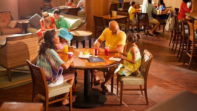 A family relaxes with drinks and a snack at Surfside Lounge, a Paradise Pier Hotel restaurant