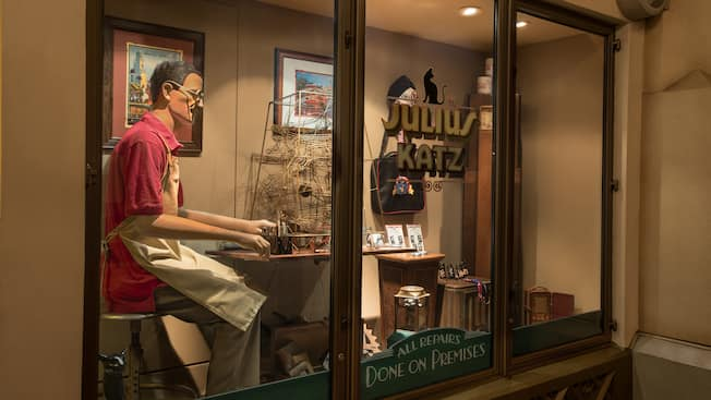 A window display at Julius Katz & Sons showcasing a mannequin crafting merchandise and souvenirs