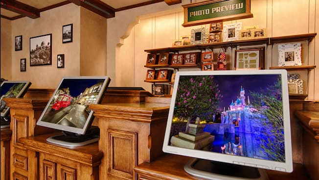 An assortment of preview screens showcasing in-park photos on a countertops at Kingswell Camera Shop