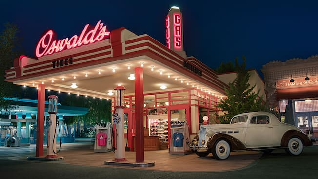 A shop that resembles a vintage gas station selling Oswald the Lucky Rabbit apparel, toys and Mickey Mouse ear hats with a classic car parked out front and signs that read ?Oswald?s?, ?Tires?, ?Batteries? and ?Gas?