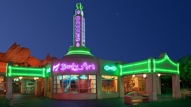 A shop that resembles a vintage gas station lit up at night by neon lights with signs that read 'Ramones' and 'House of Body Art' and featuring windows displaying custom-designed automobile hoods