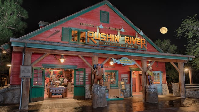 A rustic shop surrounded by trees with carved wooden bears on the porch and signs that read 'Rushin' River Outfitters', 'Eureka Gold & Timber Co.' and 'Wilderness Wear & Gear', selling apparel and hats themed to California and Grizzly River Run