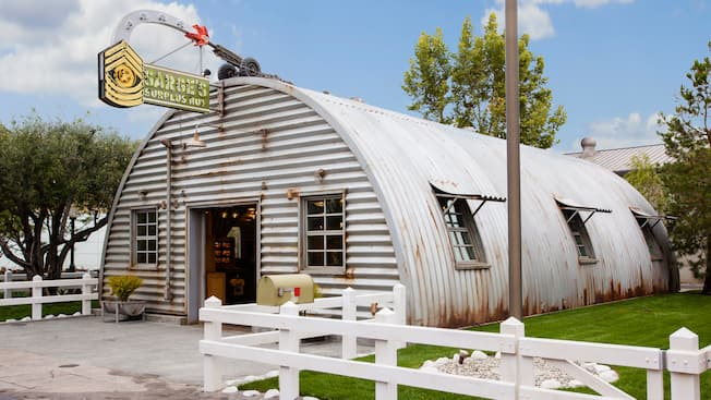 An slightly rusty corrugated metal Quonset hut with a white picket fence, mailbox, flagpole and a sign resembling a firing artillery gun that reads 'Sarge's Surplus Hut'