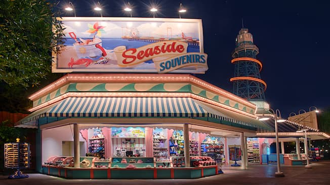 "An open-air shop selling merchandise that includes sunglasses, Mickey Mouse ear hats, novelty gloves, pins, toys and snacks, beneath a lighthouse-like tower and a huge billboard sign with an illustration of a crab, a bucket of seashells, a beach, an ocean pier and the words ""Seaside Souvenirs"""