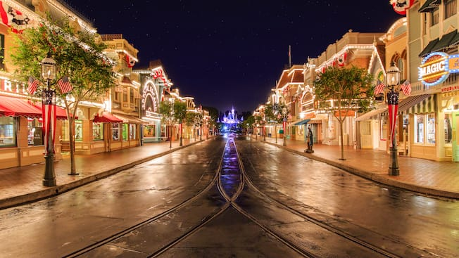 Festive lights illuminating Disneyland Park as Main Street, U.S.A. leads to Sleeping Beauty Castle