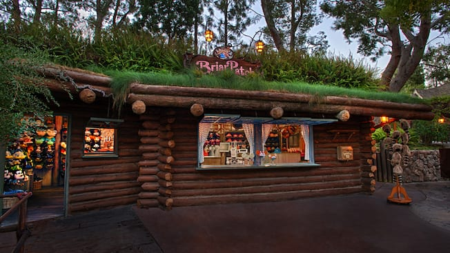 Grasses and other greenery growing along the rooftop of the log cabin-themed exterior of Briar Patch
