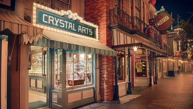 Fine crystal glassware sparkles in the evening while lining the window displays at Crystal Arts
