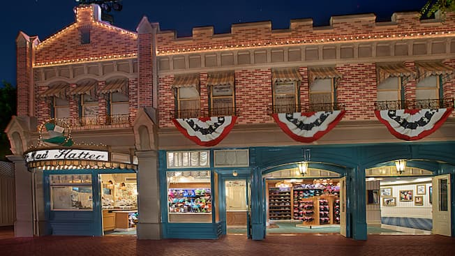 Patriotic flags cascading from the storefront as lights outside The Mad Hatter illuminate the night