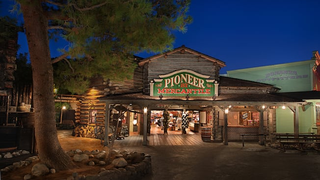 A towering pine tree stands tall directly outside the entrance to Pioneer Mercantile in Frontierland