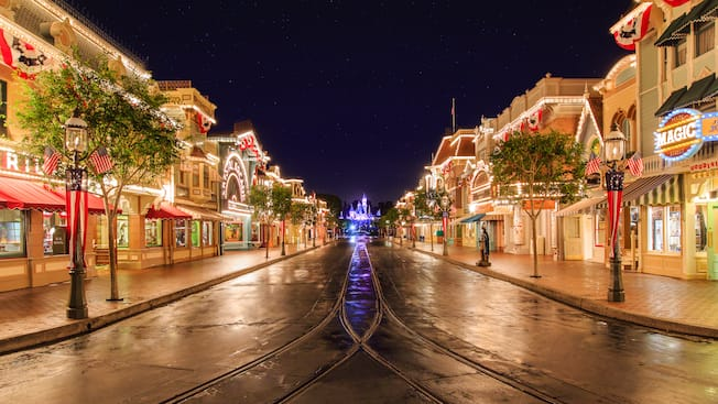 Vibrant lights line rooftops and marquees at Main Street, U.S.A. on the way to Sleeping Beauty Castle