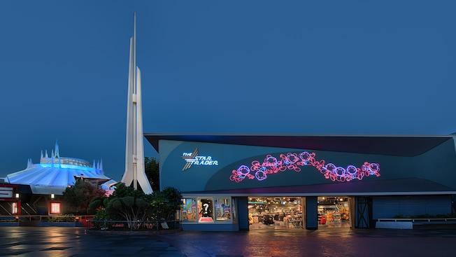 El exterior de Star Trader se ilumina de noche mientras las torres de Space Mountain se alzan hacia el cielo