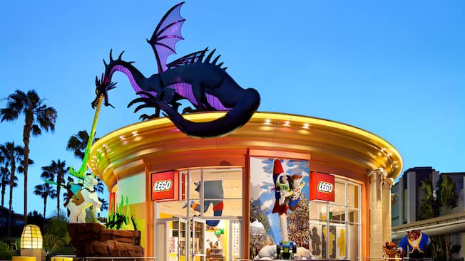A giant LEGO dragon sits above The LEGO Store door and breathes fire at a knight on horseback
