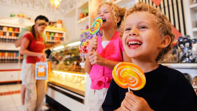 Two little kids lick oversize lollipops from Marceline's Confectionery