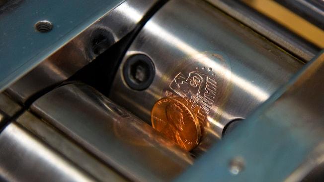 Una máquina de impresión de monedas con rodillos de acero graba un diseño de Disneyland Diamond Celebration en una moneda de un centavo
