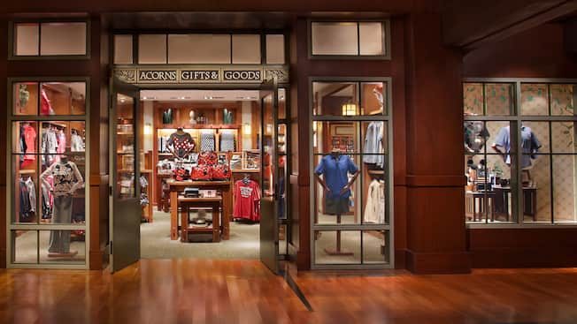 A shop accented with hardwood, a sign that reads 'Acorns Gifts & Goods' and merchandise that includes Disney-themed shirts, handbags, hats and Mickey Mouse ear hats