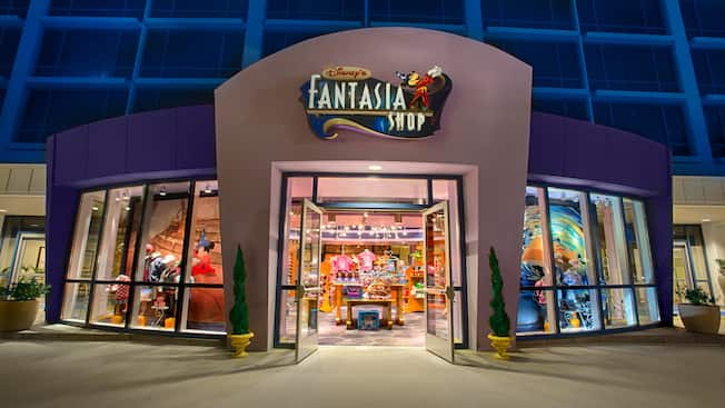 A shop at the base of a modern hotel tower with a sign featuring Mickey Mouse that reads 'Disney's Fantasia Shop' and merchandise that includes Disney-themed apparel, dolls and toys