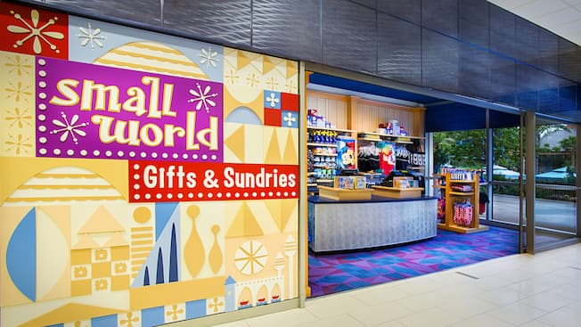 "A simple shop with a sign that reads ""small world Gifts & Sundries"" selling Disney-themed swimwear, sunscreen, towels, batteries, novelty electric fans and souvenirs"