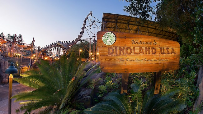 "A wooden welcome sign to ""DinoLand U.S.A.,"" with a huge dinosaur skeleton in the background"